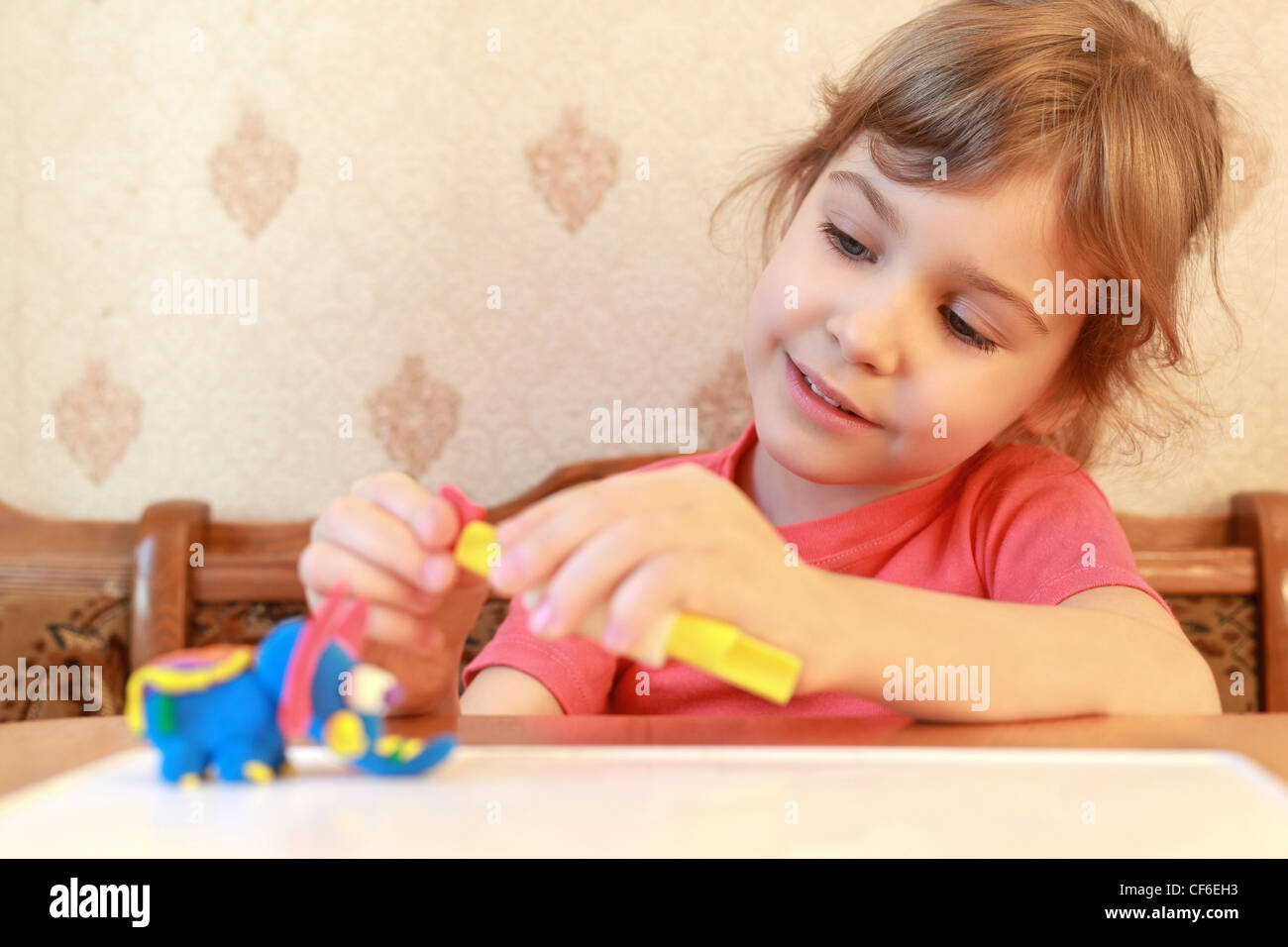 Little girl is at  table and models from plasticine, focus on  girl - Stock Image