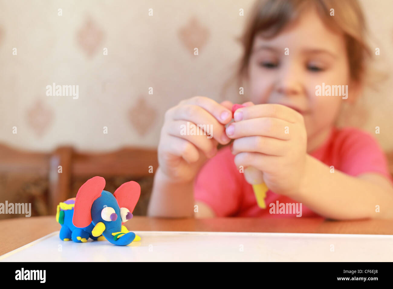 Home-made elephant which was modeling by girl on table, focus on an elephant - Stock Image