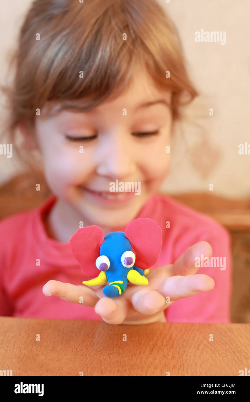 Little girl holds home-made elephant on  palm, focus on an elephant - Stock Image