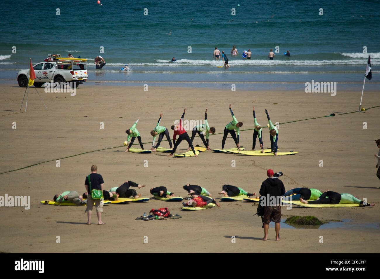 Surfers warming up on the beach at a surf school at Towan beach, Newquay. - Stock Image