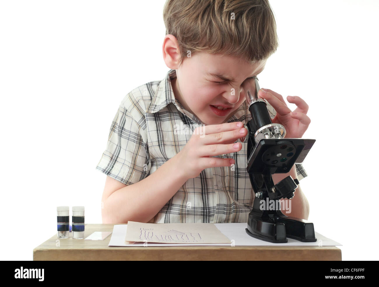 Curious little boy in checkered shirt stares into black microscope - Stock Image