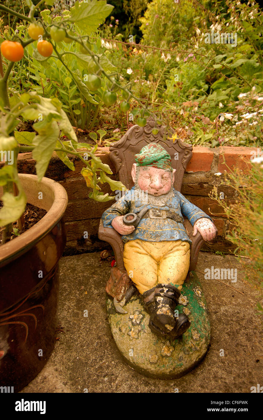 A dozing garden gnome, next to a garden pot and in the shade of a ...