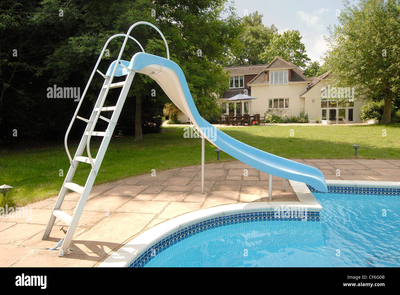Outdoor pool with slide  An outdoor swimming pool in a garden featuring a slide, plants and ...