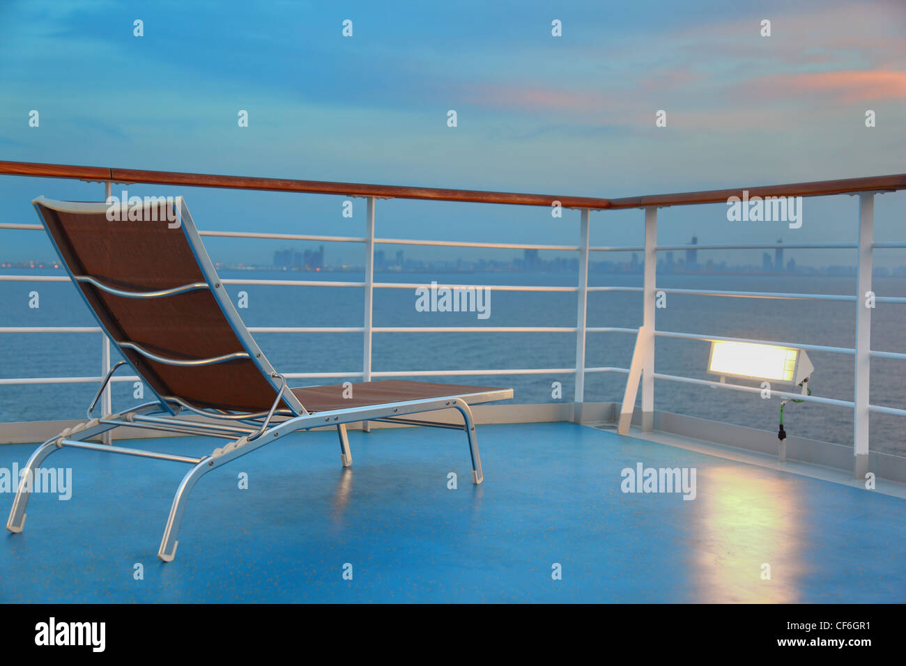 Illuminated solitary deck-chair on ship overlooking city at evening - Stock Image