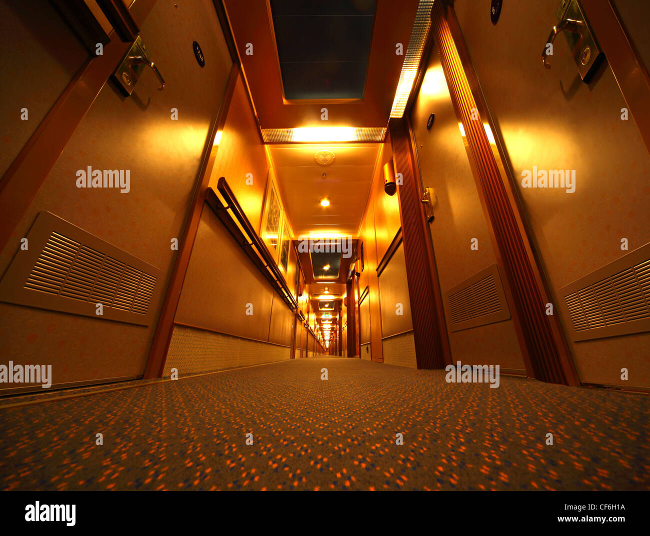 Narrow and long illuminated corridor with hotel rooms in cruise ship - Stock Image