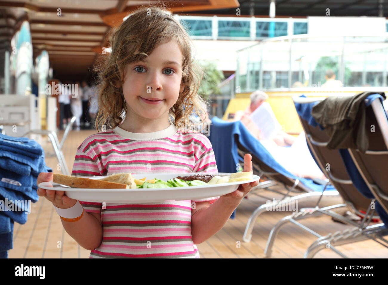 little girl standing and holding tray with food on cruise liner deck, half body - Stock Image