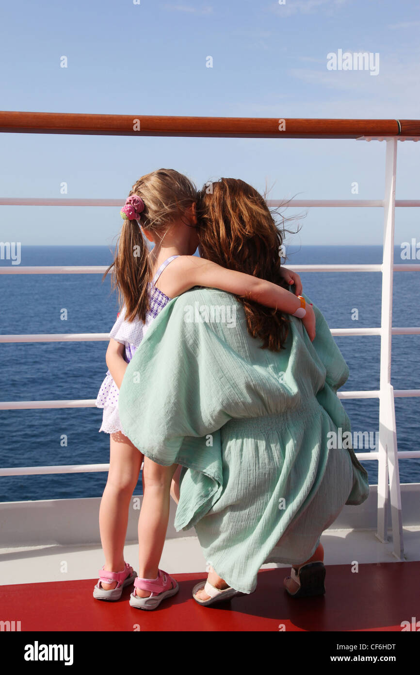 daughter and mother embracing on cruise liner deck, view from back, sunny day - Stock Image