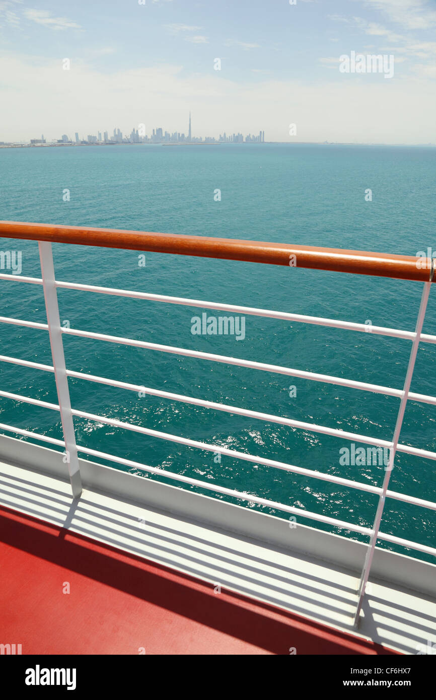 cruise liner deck with red floor and wooden rail, sunny day, city on horizon - Stock Image