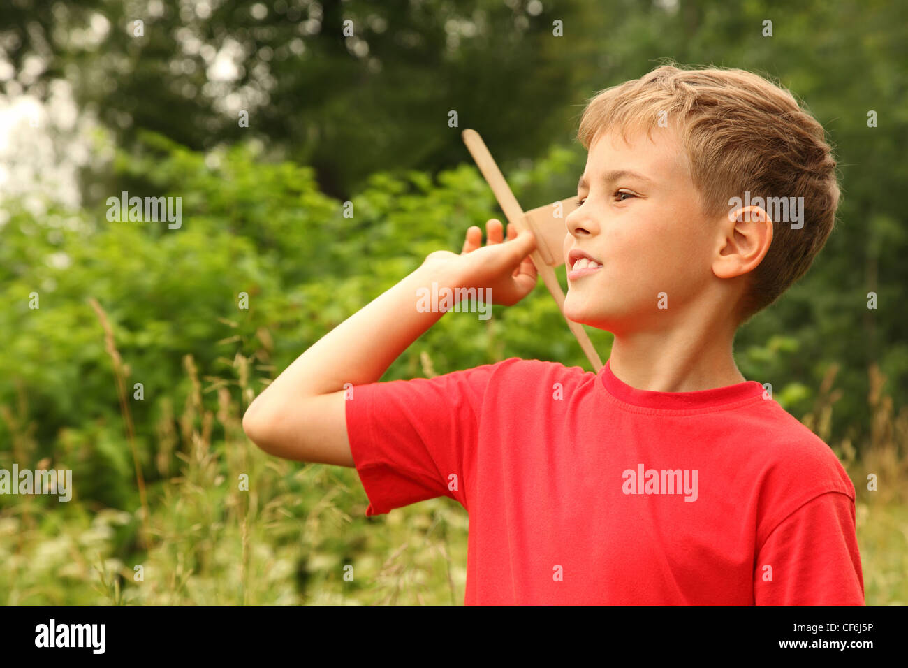 little boy in red T-shirt plays with wooden airplane on nature - Stock Image