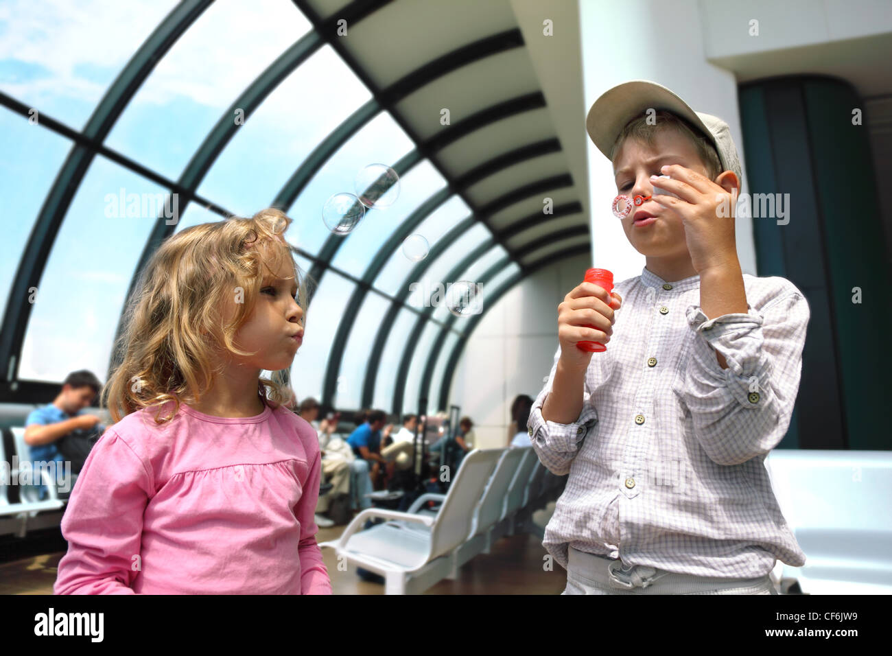 Blondy little boy and girl blow up soap bubbles inside airport - Stock Image