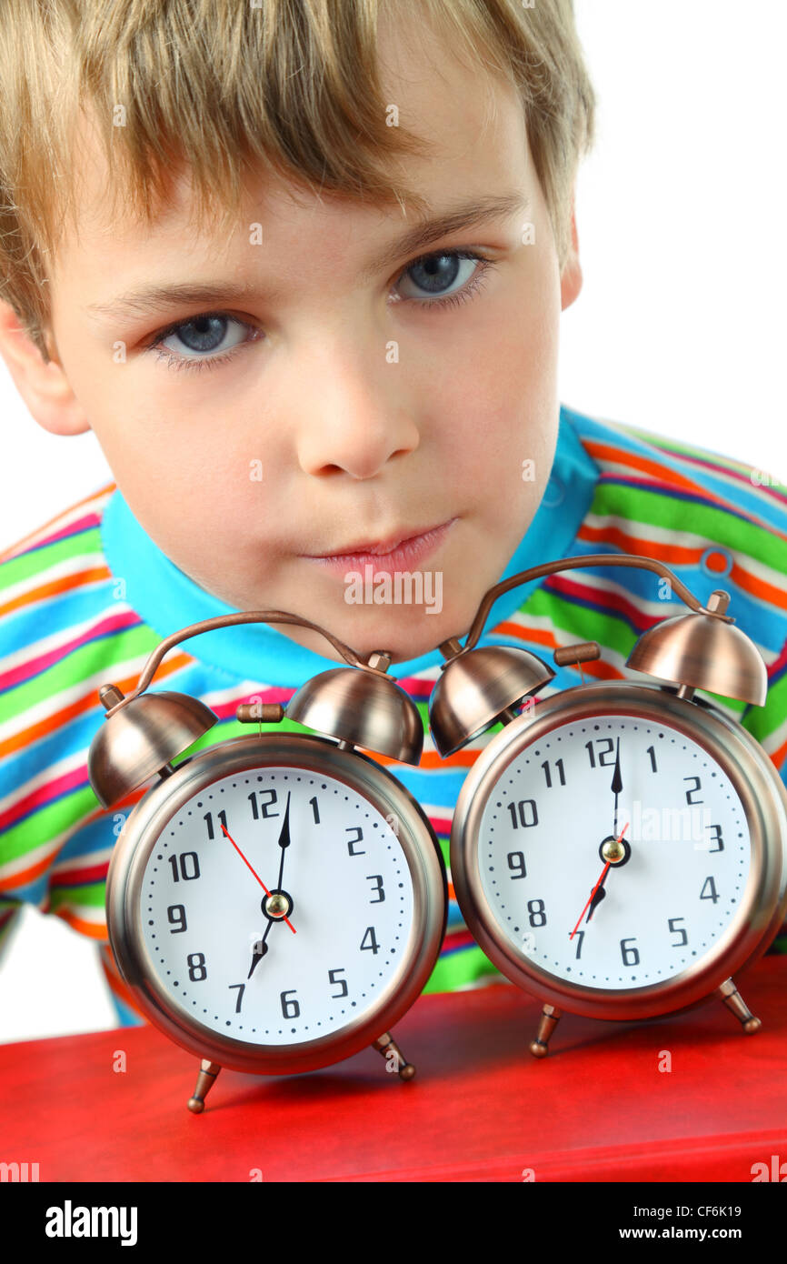 Little blond boy in striped shirt laid his head on two alarms - Stock Image