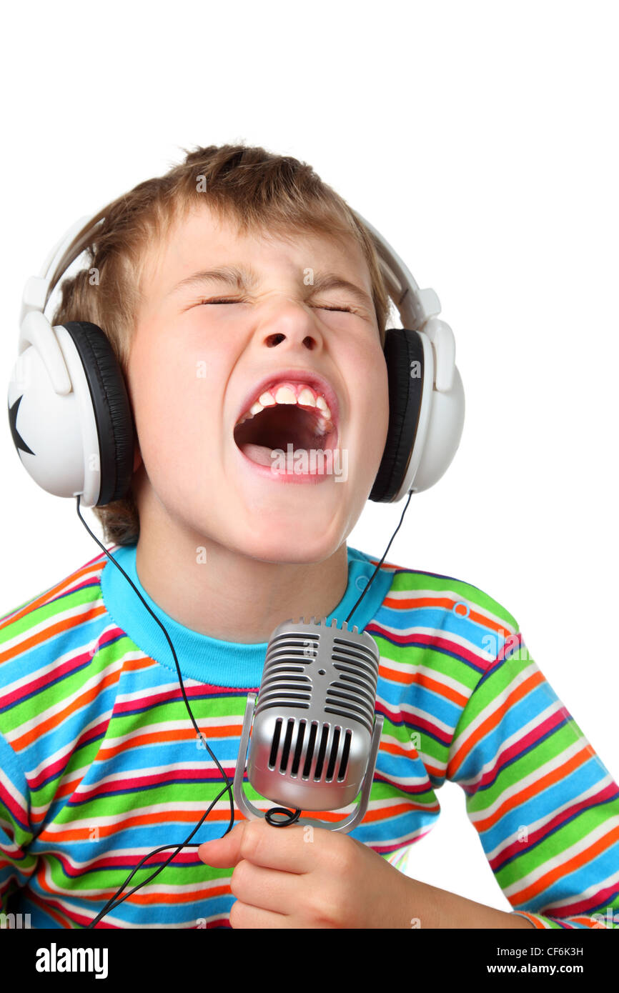 Little boy in headphone with microphone in hands sings with wide open mouth - Stock Image