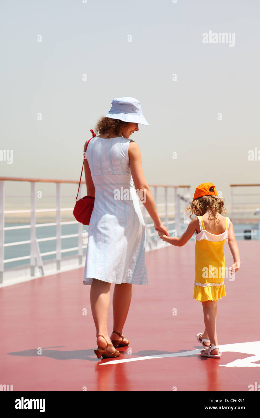 young mother and daughter walking on cruise liner deck, sunny day, view from back - Stock Image