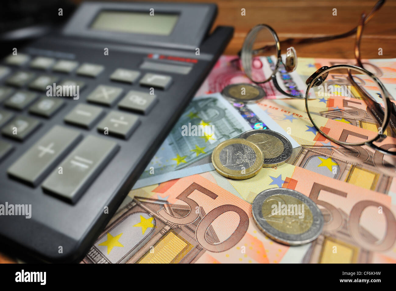 Conceptual image with banknotes and coins in euro currency and calculator to illustrate bank crisis in European - Stock Image