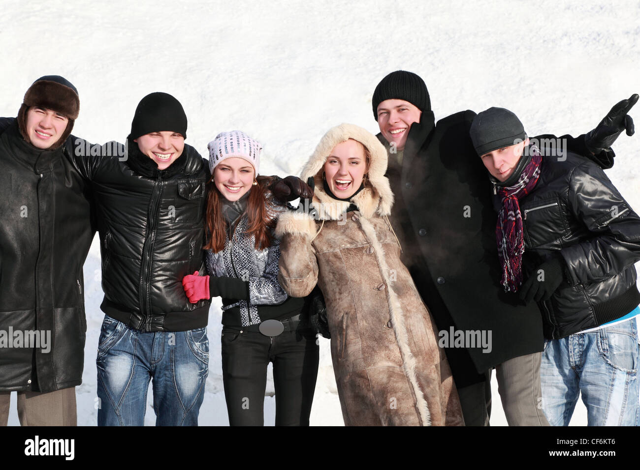 Students stand together hugging hands and laugh - Stock Image