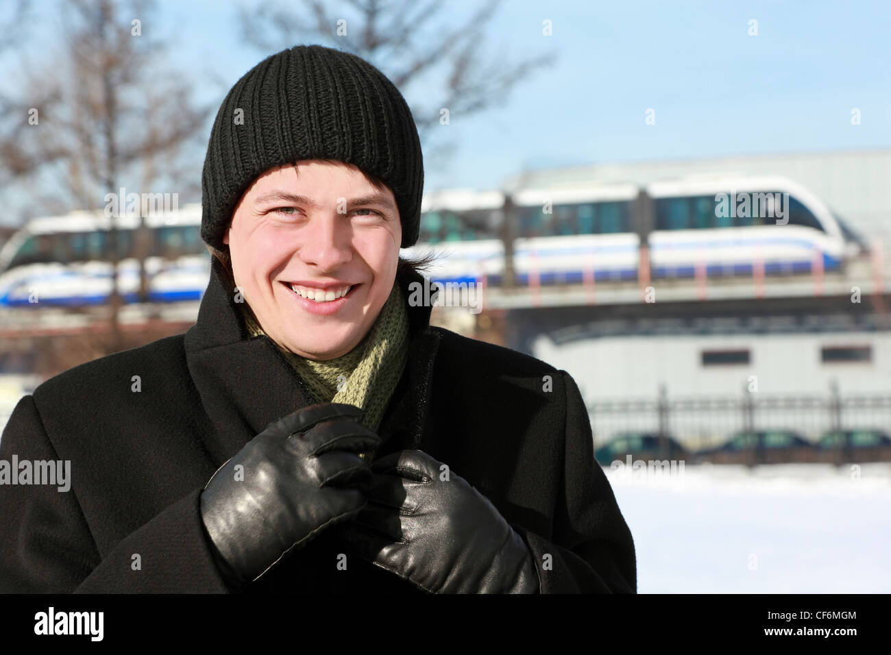 Young man stands near  station of speed streetcar and supports collar - Stock Image