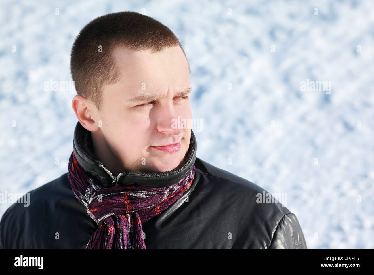 Young man stands on snow in winter and dreamily looks far - Stock Image