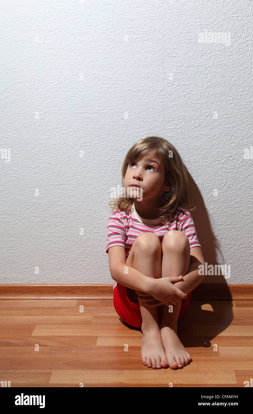 Little girl in casual clothes looks sad to corner, whence comes the light - Stock Image