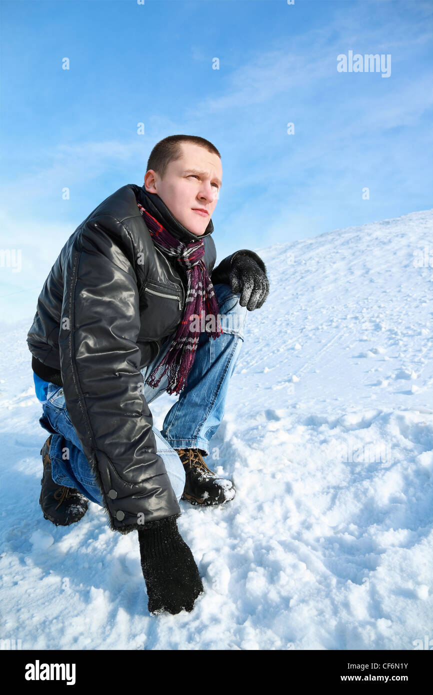 Man concentrated looks  winter of squatting  in sky and leans  hand on snow - Stock Image