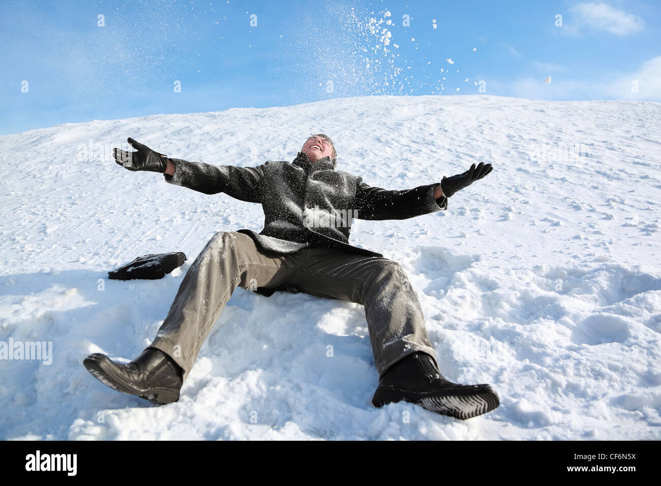 Student sits on snow by winter day and merrily throw him in sky - Stock Image