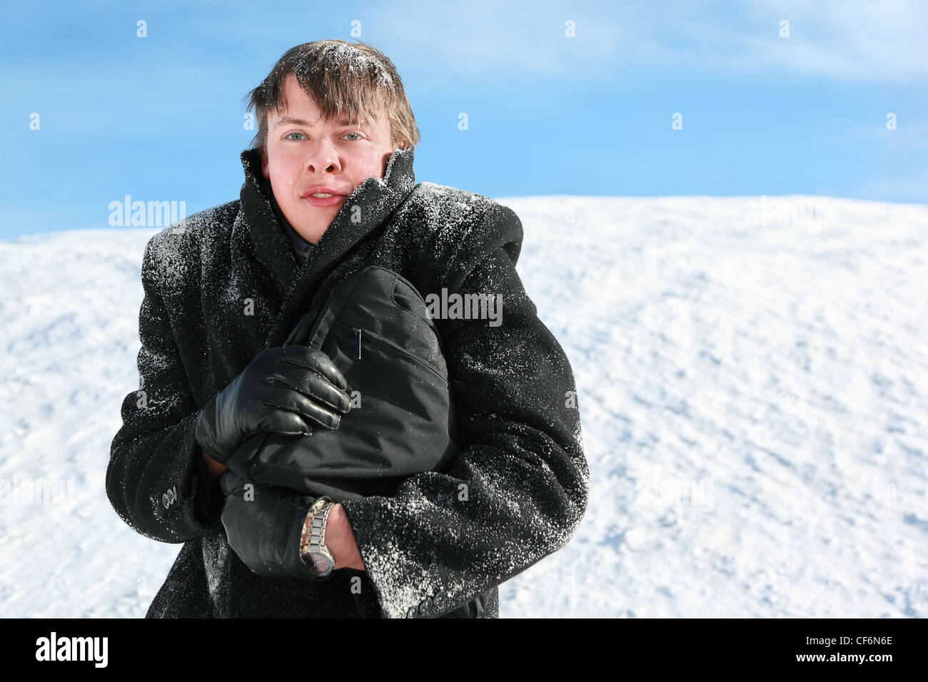Young man gets on hip brief-case and hides head from frost in collar - Stock Image