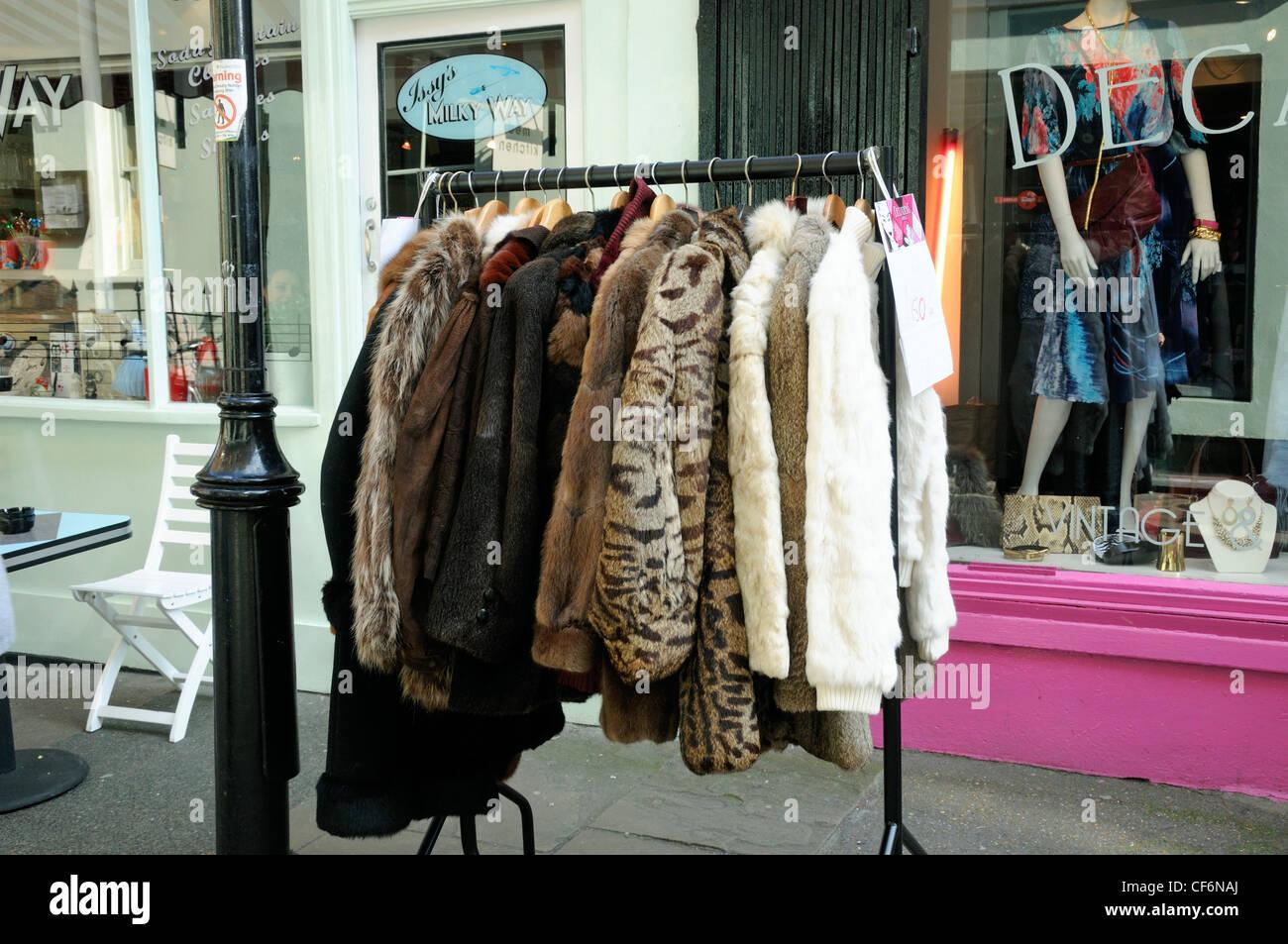 Vintage fur coats for sale on clothes rack outside shop in Camden Passage Islington London England UK - Stock Image