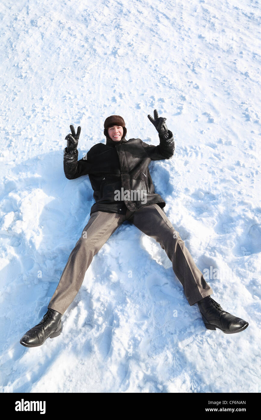 Youth lies on snow on back and shows hands gesture of victory and laughs - Stock Image