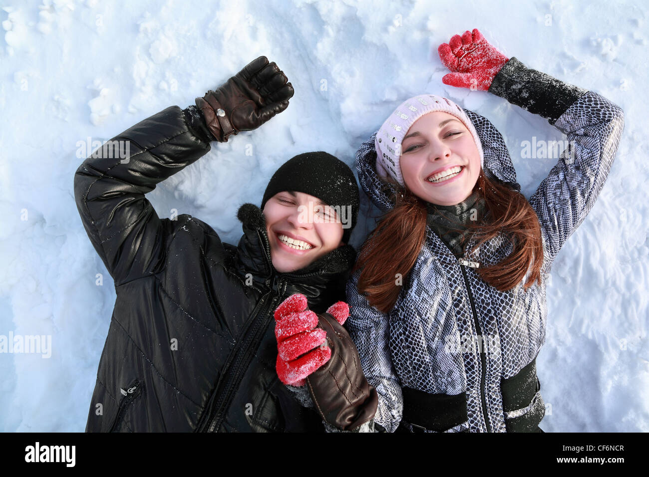 Two lovers people lie on in winter on snow  holding  hands and smile - Stock Image