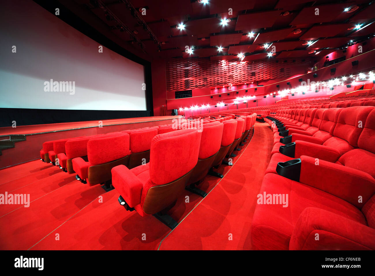 View from stairs on rows of comfortable red chairs in illuminate red room cinema - Stock Image