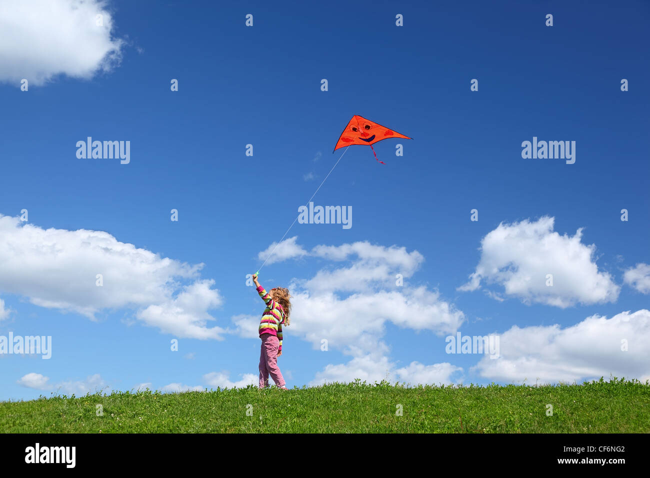 Little girl starts air serpent in sky in summer - Stock Image
