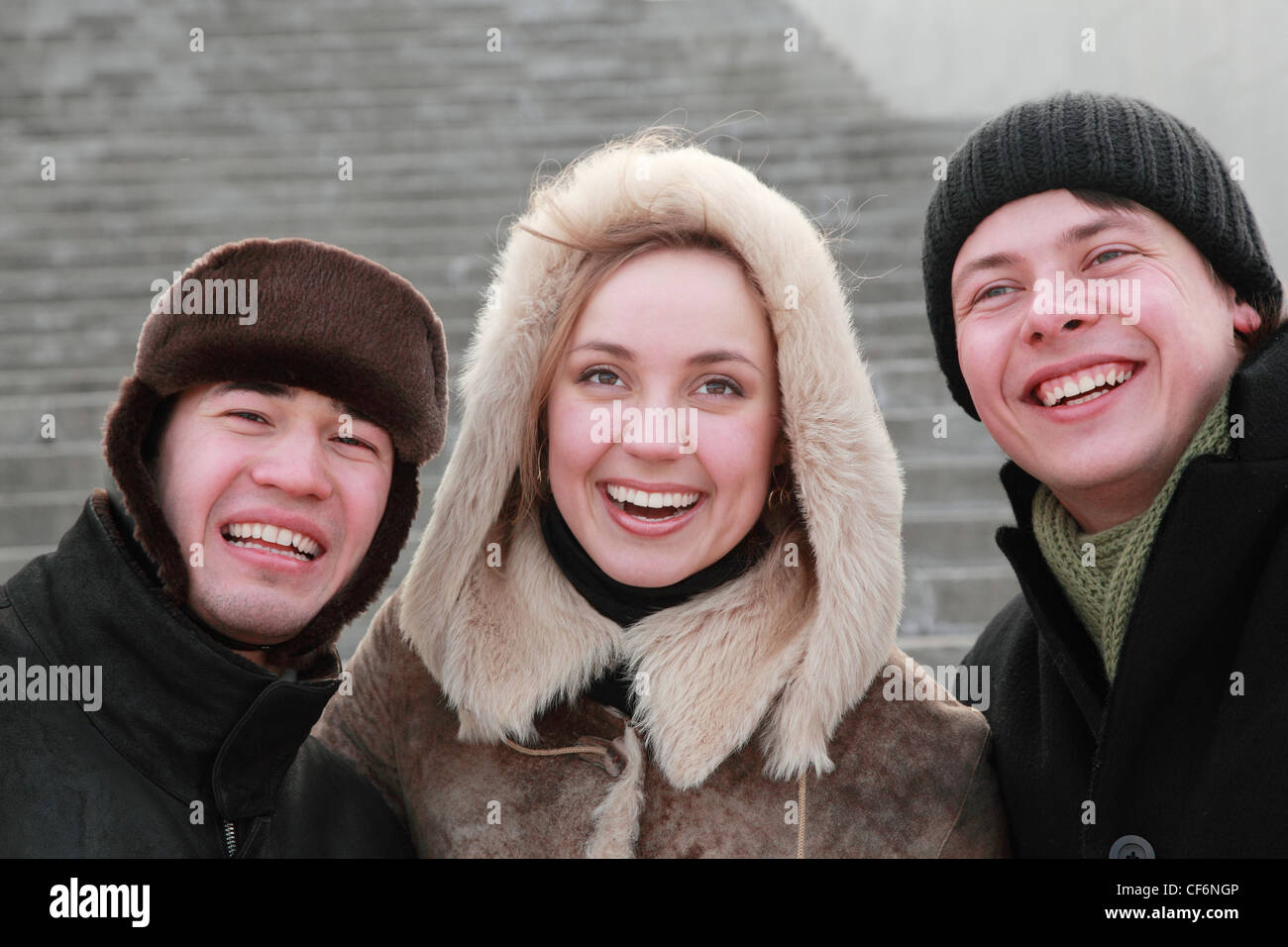 encounter of old friends after long years of separation, trio in winter clothes - Stock Image
