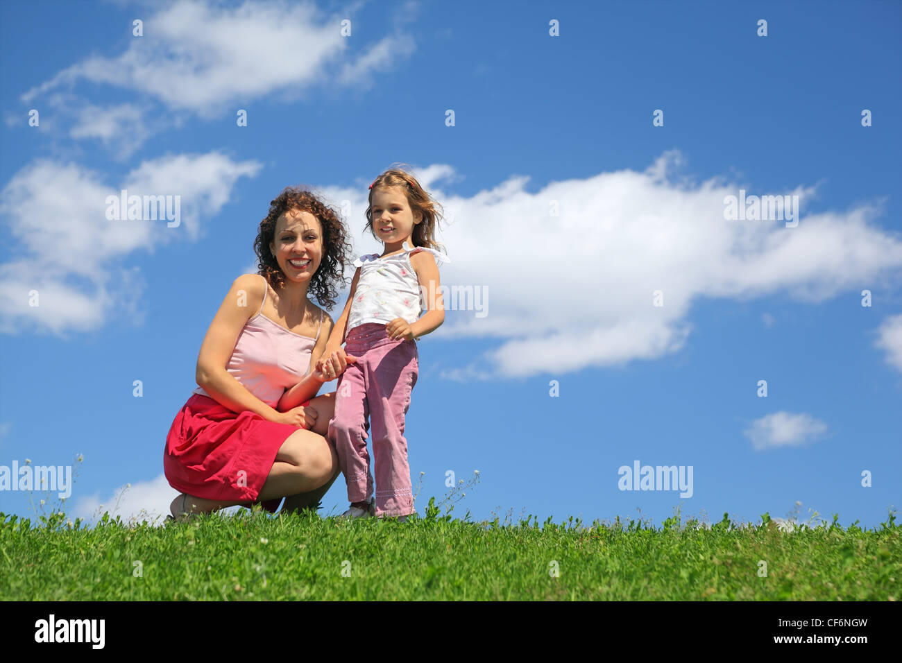 Mother squatting alongside with daughter holds it for hand and laughs - Stock Image