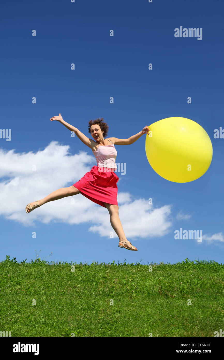Woman in summer pushes off from earth and on wing holds  yellow inflatable ball Stock Photo