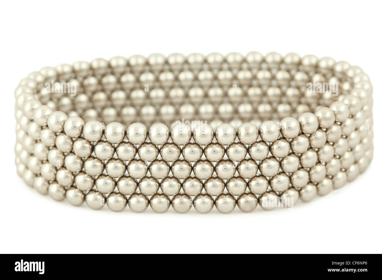 Bangle from silvery beads lies on  white background - Stock Image