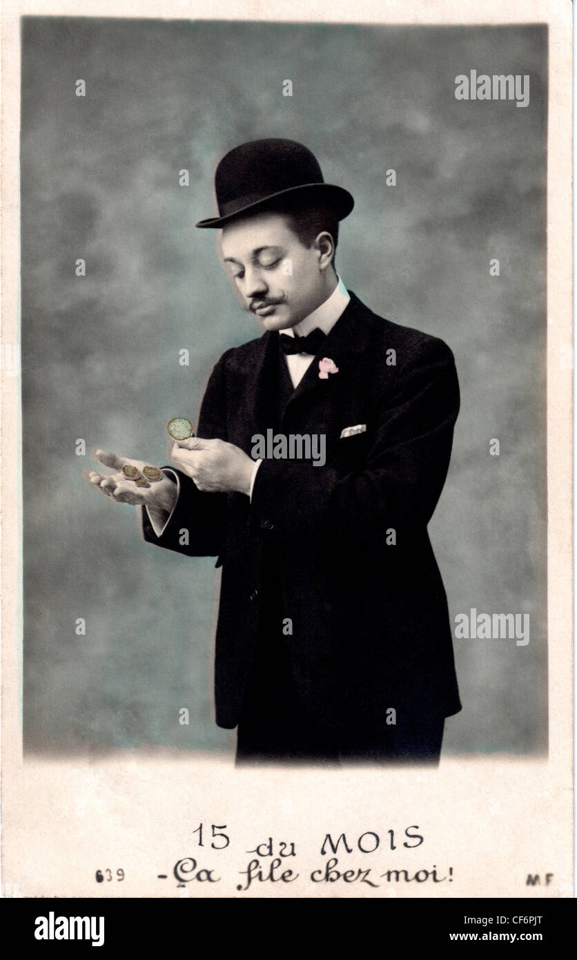 A vintage photo of a man wearing a suit and top hat counting his money, circa 1907. - Stock Image