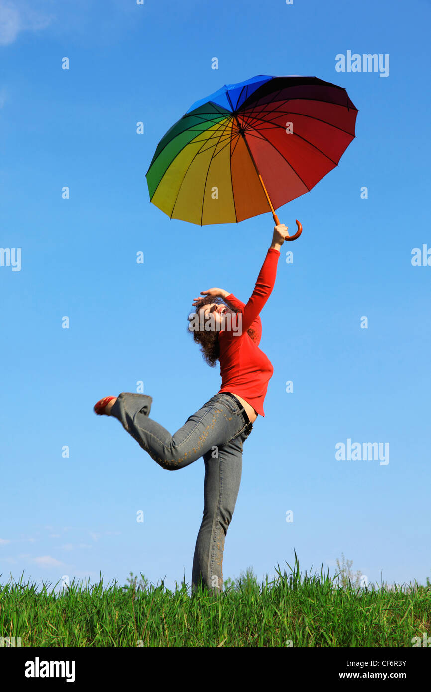 girl standing on one leg on green grass with colorful umbrellas aloft in hand against blue sky - Stock Image