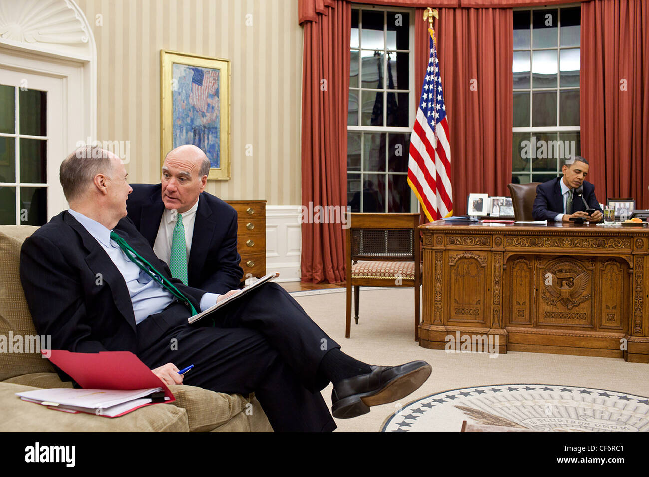Chief of Staff Bill Daley confers with National Security Advisor Tom Donilon, left, as President Barack Obama talks - Stock Image