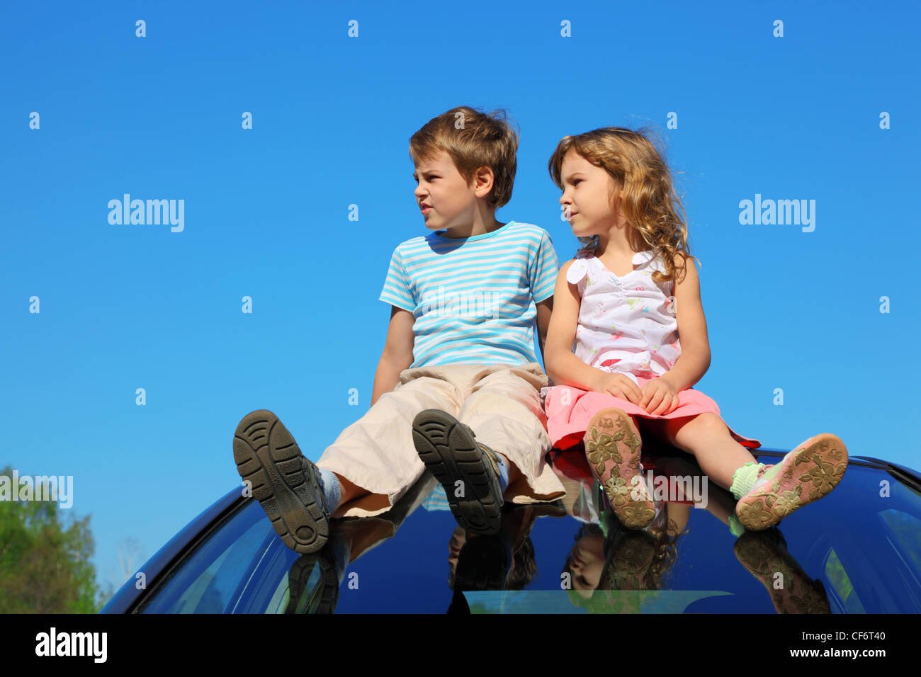 little boy and girl sitting on car roof on blue sky, looking to left side - Stock Image