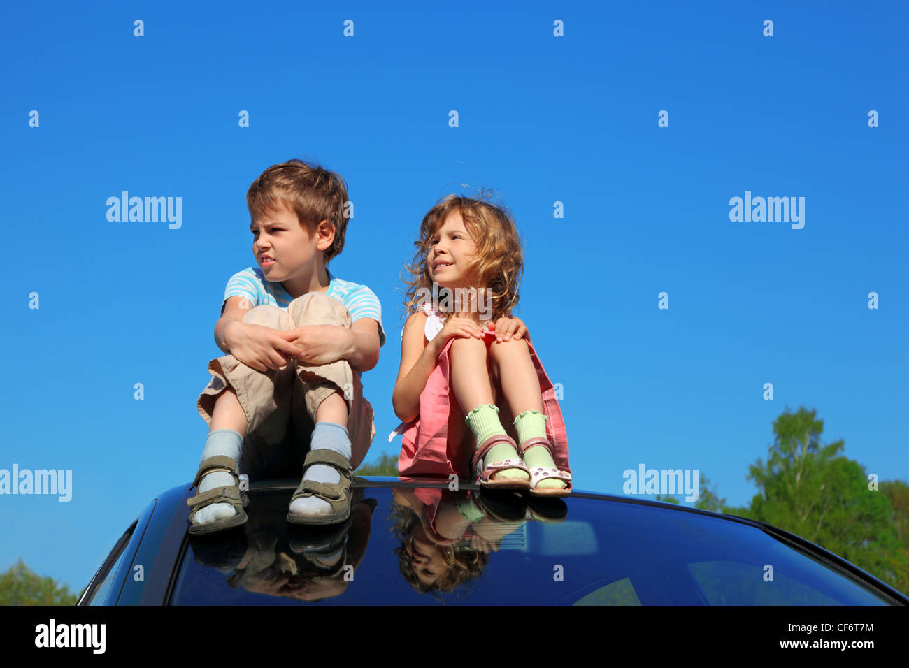little boy and girl sitting on car roof on blue sky, hands on legs Stock Photo