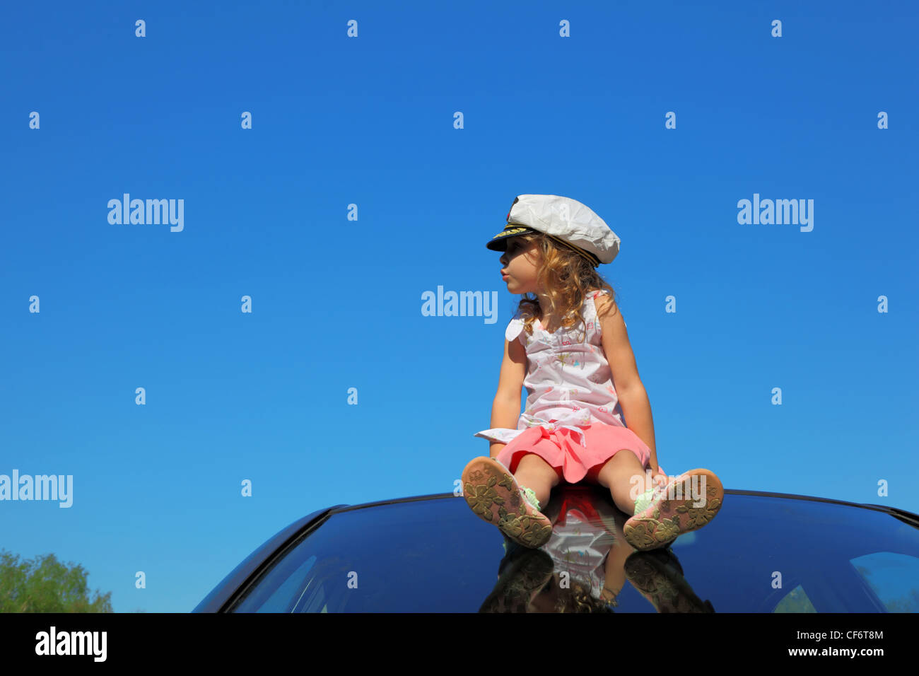 little girl with captain cap sitting on car roof watching on left side, blue sky Stock Photo