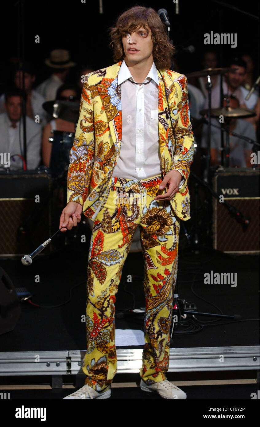 d89fdd273149d Paul and Joe Paris Menswear S S Male model swinging a microphone wearing a  rockstar style yellow floral print suit white shirt