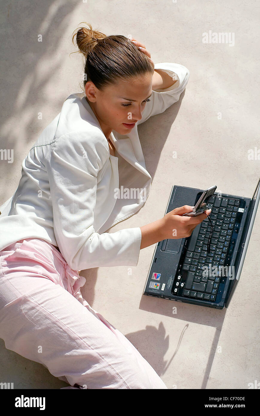 Brunette female wearing a white zip up top and light pink trousers, lying on the floin front of lap top and using - Stock Image