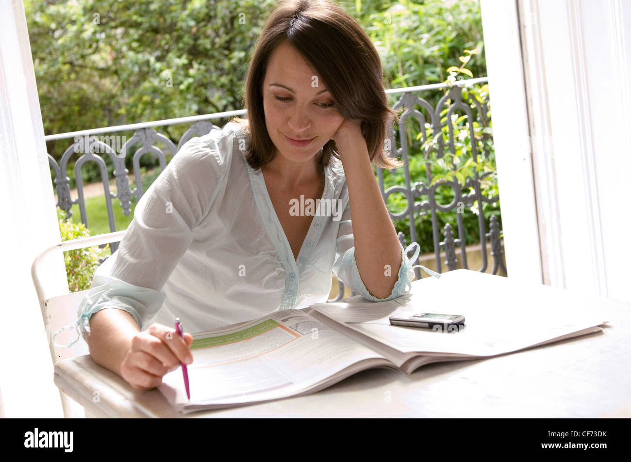 Female sitting at a table, job hunting in a newspaper - Stock Image