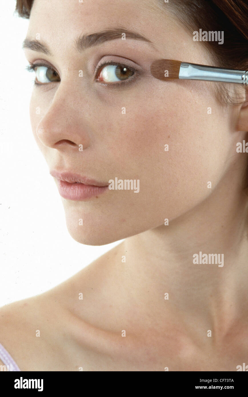 A close up image of female's face, applying shimmering eyeshadow with make up brush, unsmiling, looking at camera - Stock Image