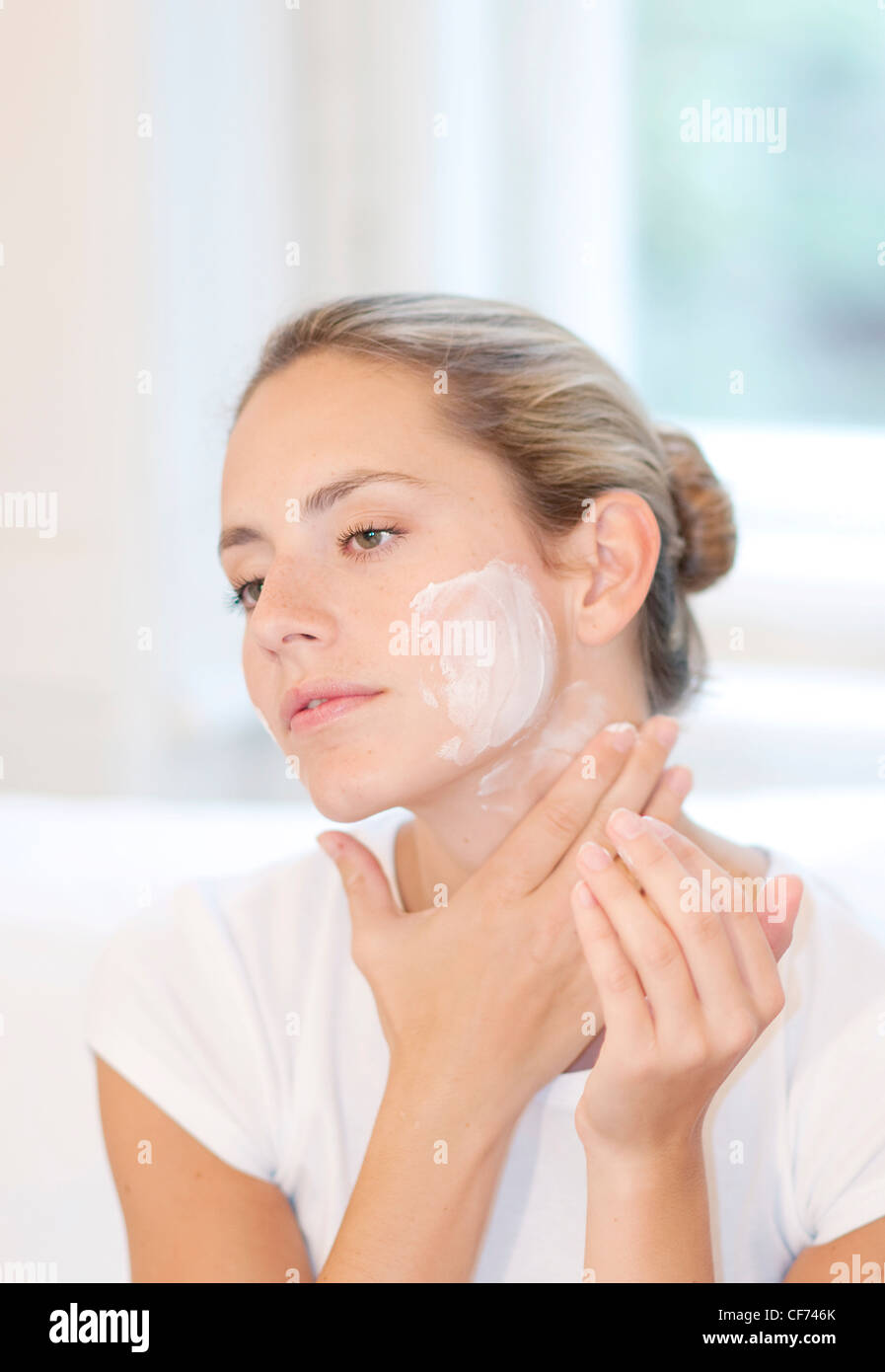 Female highlighted fair hair off her face, wearing a white t shirt, applying face cream to her cheeks and neck, - Stock Image