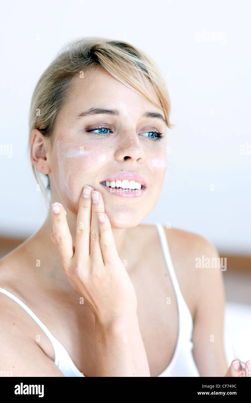 Female with fair hair tied at the back, applying face cream to her chin, smiling - Stock Image