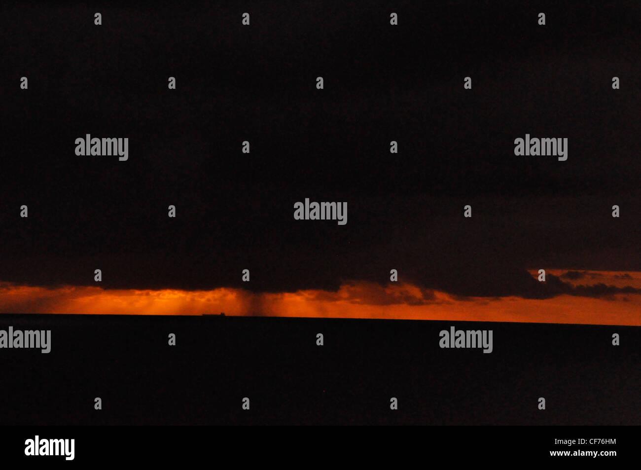 Black Sky & Sea Blazing orange clouds dramatic moody - Stock Image