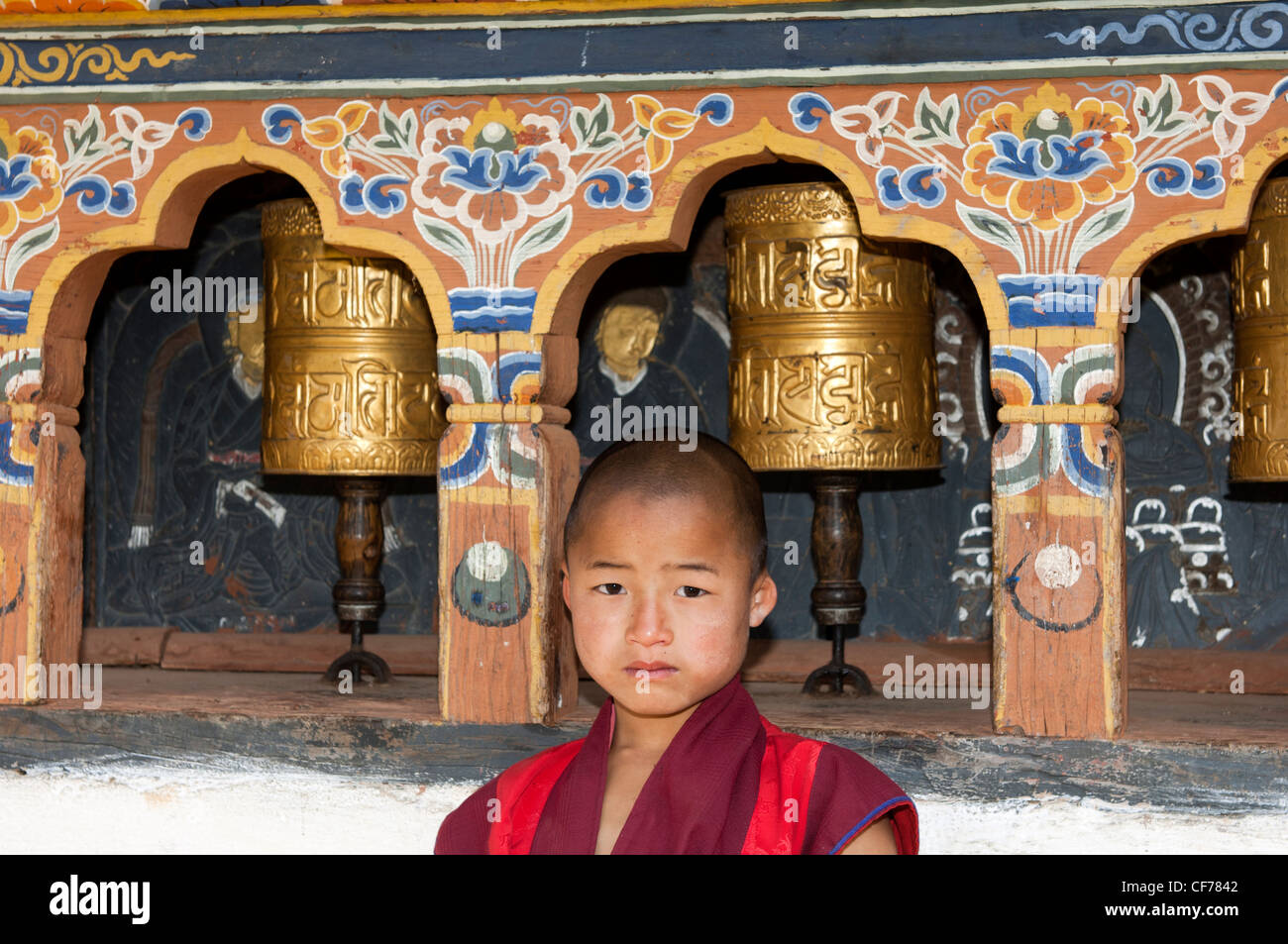 Infantile Buddhist monk standing by the prayer mills in the Temple of Fertility Chimi Lhakhang, Lobesa, Bhutan - Stock Image
