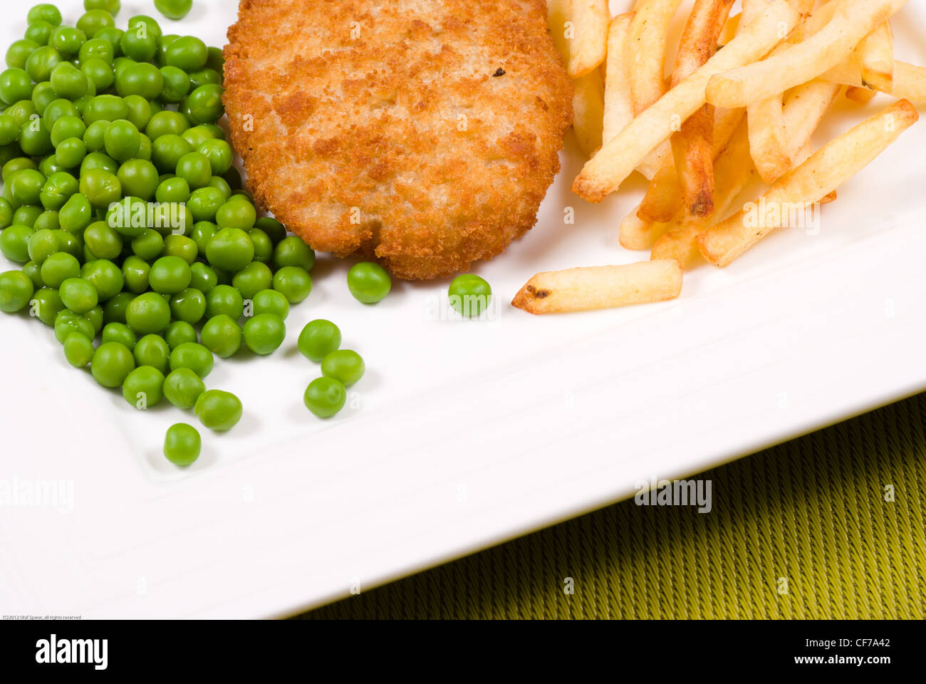 Fish and chips, battered hake with garnish - Stock Image