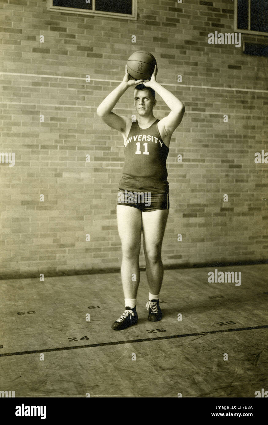 University basketball player holding basketball during portrait in 1945 or 1946 sports player 1940s - Stock Image